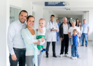 Happy Latin American family doctor with a baby at the hospital looking at the camera smiling - healthcare and medicine